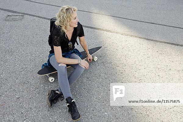 Auf dem Skateboard sitzende Skateboardfahrerin
