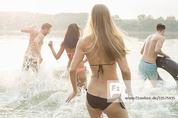 Freunde haben Spaß mit aufblasbarem Ring im Fluss