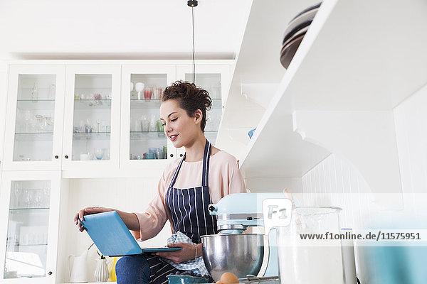Junge Bäckerin sitzt auf der Küchentheke und schaut auf den Laptop