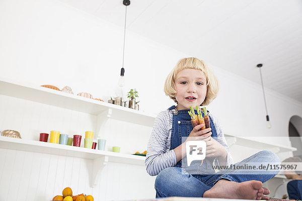 Porträt eines süßen Mädchens  das auf dem Küchentisch sitzt und einen Strauß bunter Karotten hält