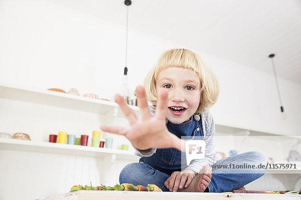 Porträt eines niedlichen Mädchens  das auf dem Küchentisch sitzt und die Hand ausstreckt