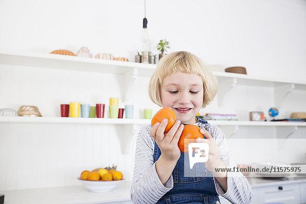 Geschnittenes Mädchen schaut sich in der Küche Orangen an