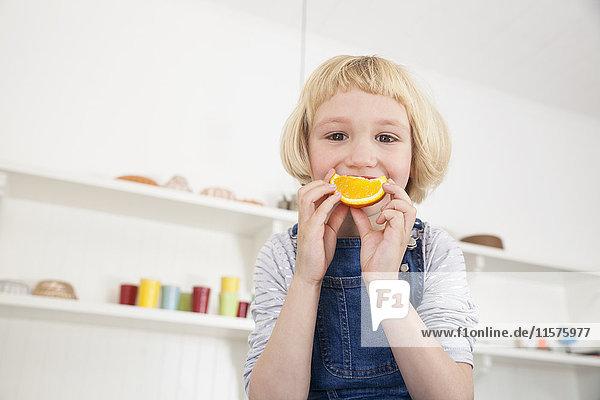 Porträt eines süßen Mädchens in der Küche  das eine Orangenscheibe an den Mund hält