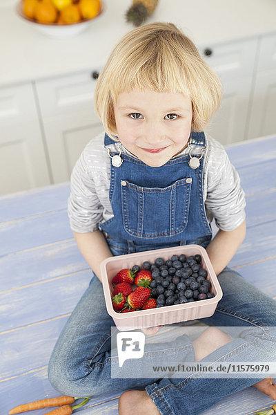 Porträt eines süßen Mädchens  das auf der Küchentheke ein Kännchen mit Blaubeeren und Erdbeeren hält