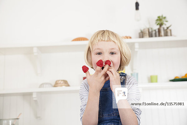 Porträt eines süßen Mädchens mit Himbeeren an den Fingern in der Küche