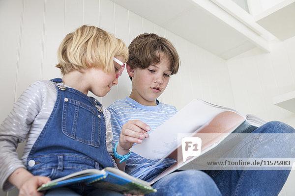 Mädchen liest Märchenbuch mit Bruder auf dem Küchentisch