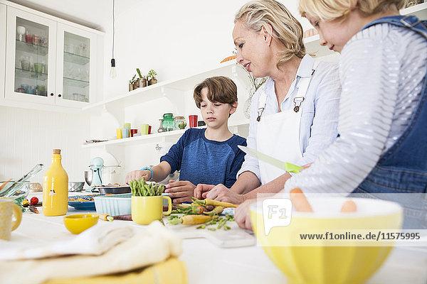 Reife Frau bereitet mit Sohn und Tochter Gemüse am Küchentisch zu
