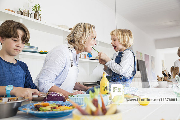 Girl feeding mother asparagus at kitchen table