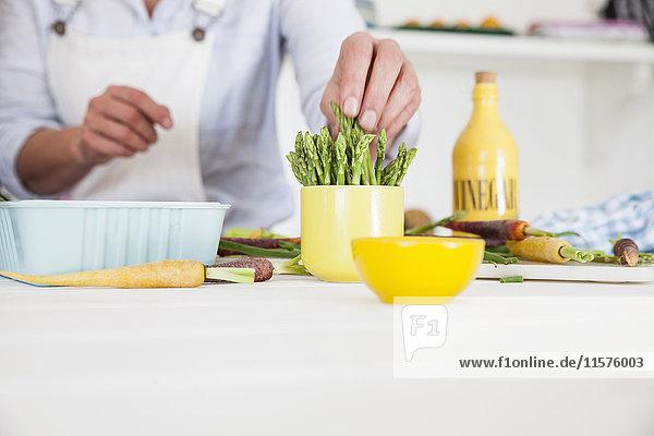 Mittelteil einer Frau  die am Küchentisch Spargel zubereitet