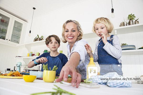 Reife Frau greift mit Sohn und Tochter am Küchentisch nach Spargel