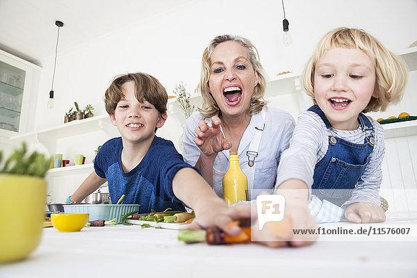Mädchen und Bruder greifen nach Gemüse  während sie mit der Mutter am Küchentisch Essen zubereiten