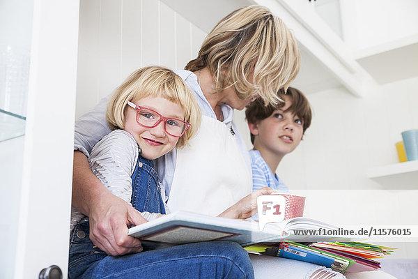 Reife Frau sitzt auf der Küchentheke und liest mit Sohn und Tochter Märchenbücher
