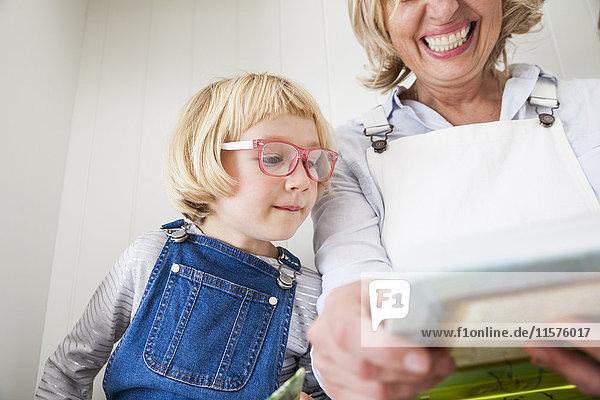 Reife Frau sitzt auf der Küchentheke und liest mit ihrer Tochter Märchenbuch