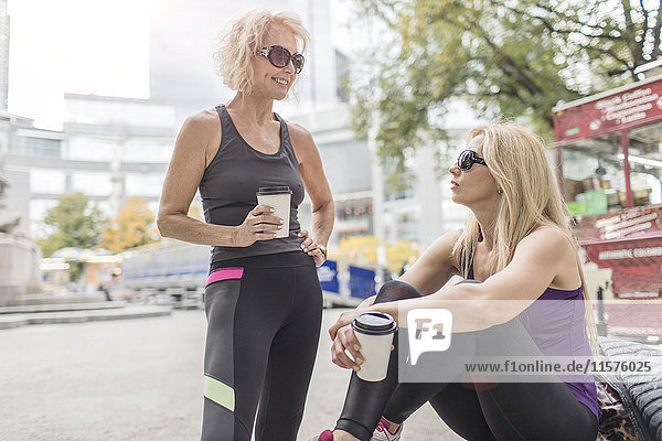 Two mature female friends training in city  chatting with takeaway coffee