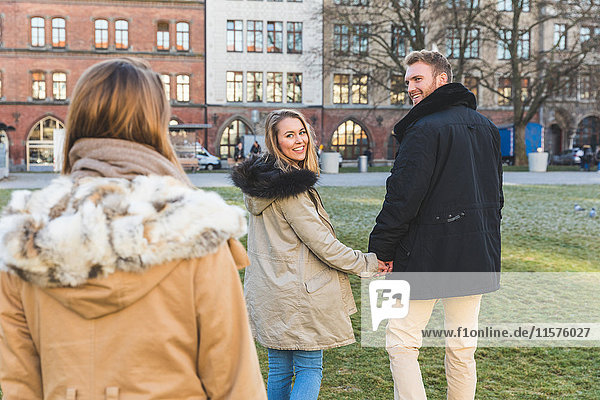 Young couple looking back at friend in city