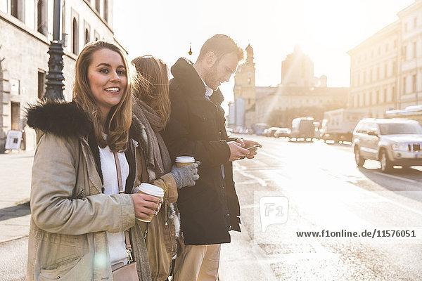 Junger Mann und Freundinnen mit Kaffee zum Mitnehmen auf dem Bürgersteig der Stadt