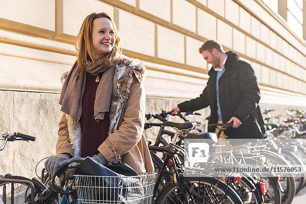 Junge Frau entriegelt Fahrrad vom städtischen Fahrradpark