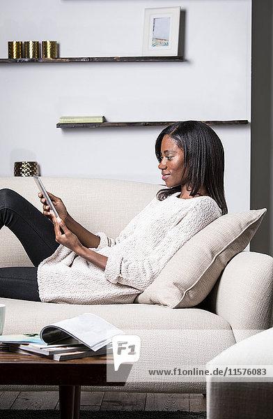 Junge Frau entspannt auf dem Sofa  mit digitalem Tablett