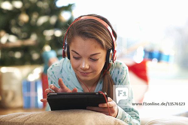 Girl lying on living room floor using digital tablet touchscreen at christmas