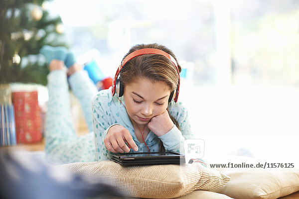 Girl lying on living room floor looking at digital tablet at christmas