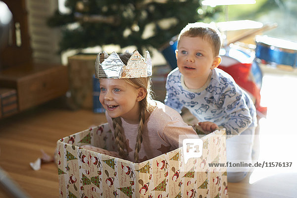 Boy pushing sister in cardboard box at christmas