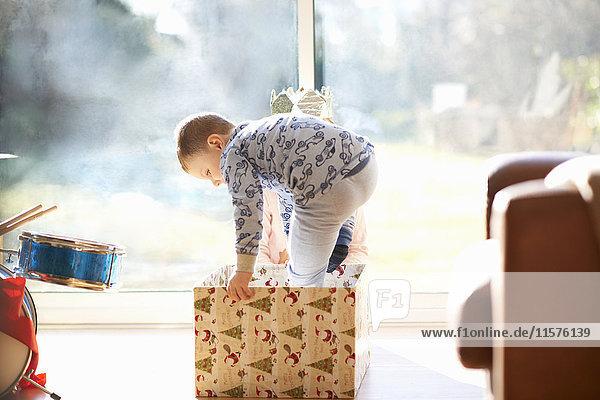 Boy and sister stepping into cardboard box at christmas