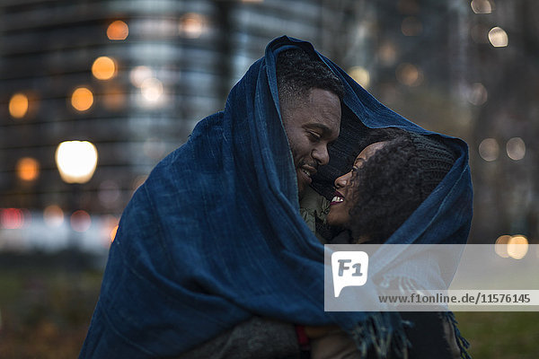 Romantic couple wrapped in blanket in city at night
