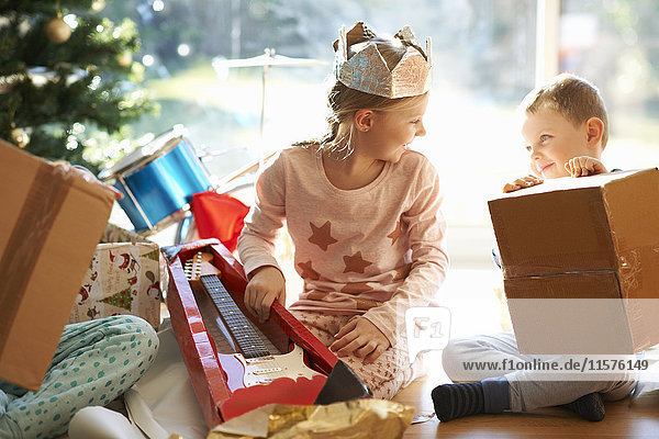 Boy and sister sitting on living room floor opening christmas gifts