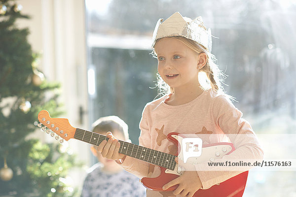 Girl playing with toy guitar on christmas day