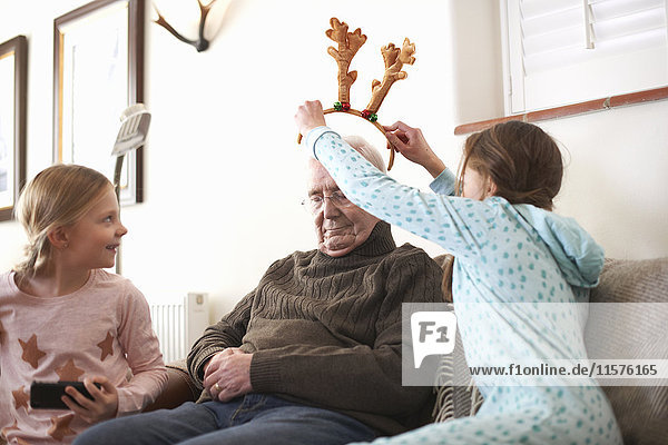 Sisters putting reindeer antlers on sleeping grandfather