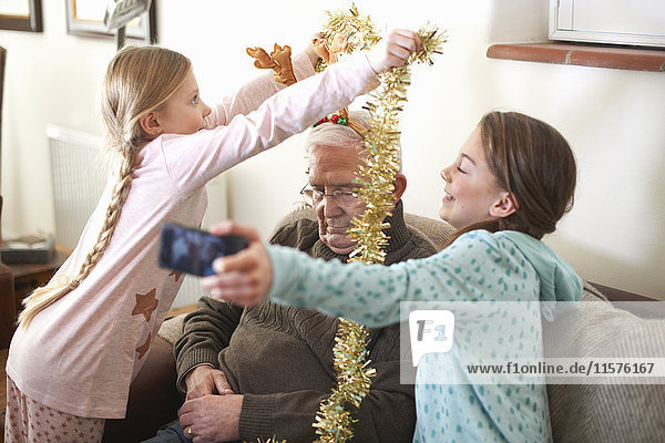 Sisters taking smartphone selfie while putting tinsel on sleeping grandfather