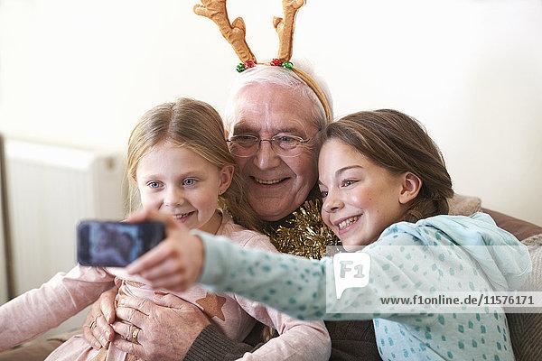 Sisters taking smartphone selfie with grandfather in reindeer antlers