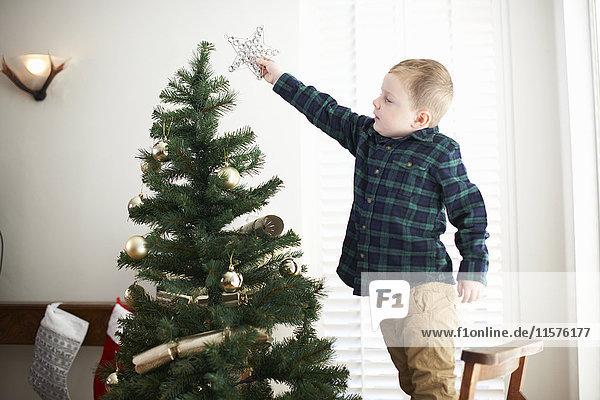 Junge steht auf Stuhl  um Stern auf Weihnachtsbaum zu platzieren
