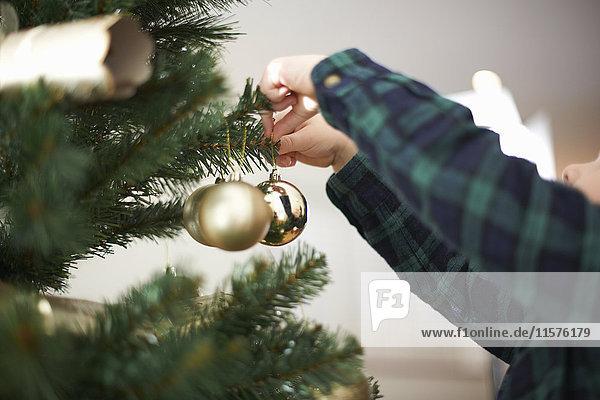 Hände eines Jungen legen Kugeln auf Weihnachtsbaum