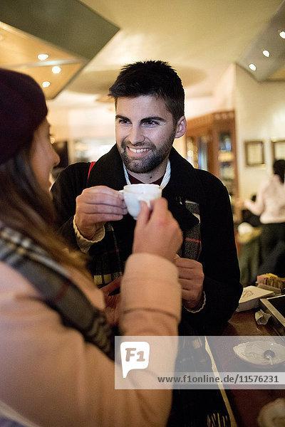 Junges Paar röstet sich im Café mit Espresso