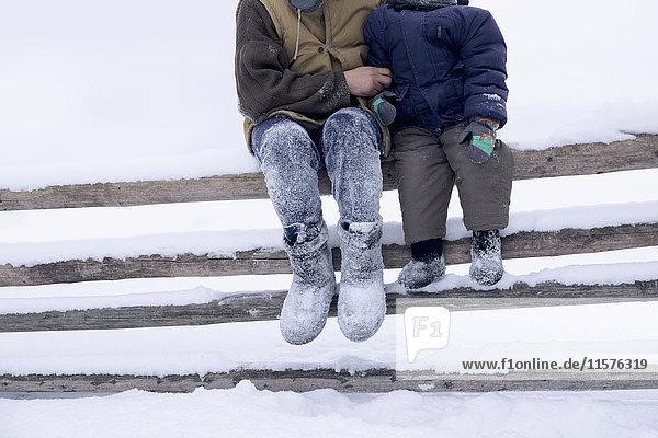 Vater und Sohn sitzen auf einem Zaun in schneebedeckter Landschaft
