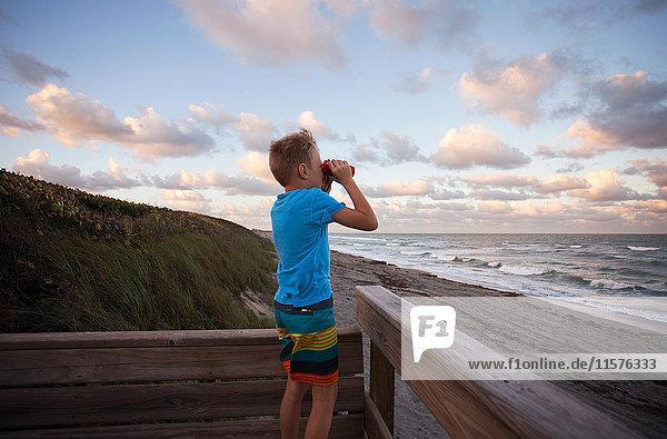 Boy at beach looking at view through binoculars  Blowing Rocks Preserve  Jupiter  Florida  USA