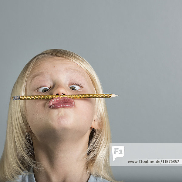 Portrait of boy balancing pencil on puckered lips