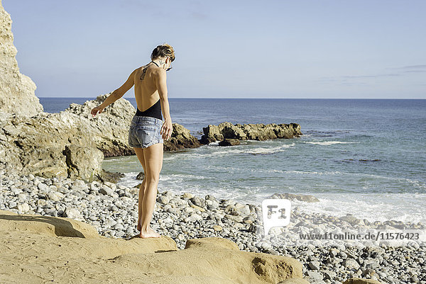 Young woman standing on rocks at beach  rear view