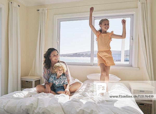 Mutter und Sohn sehen Mädchen auf dem Bett hüpfen