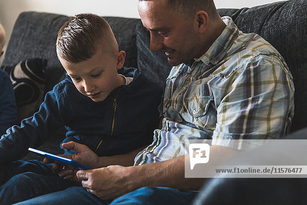 Father and son sitting on sofa  looking at digital tablet