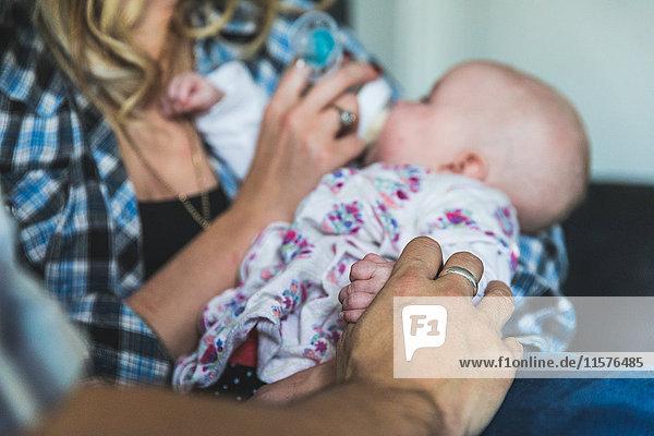 Mutter und Vater auf Sofa sitzend mit Baby-Tochter  Mutter füttert Baby mit Flasche  Mittelteil