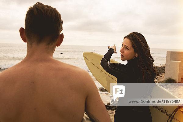 Zwei Freunde gehen auf das Meer zu  Surfbretter tragend  Rückansicht