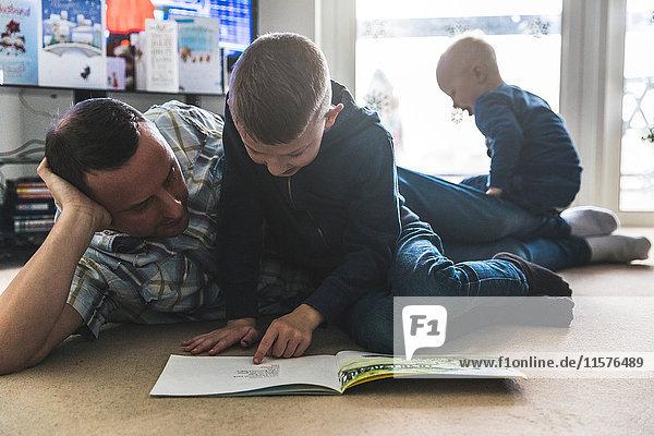 Vater hört Sohn beim Lesen eines Buches zu  jüngerer Sohn spielt im Hintergrund