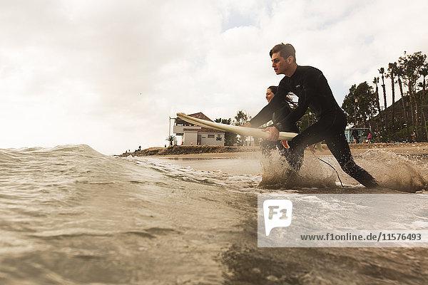 Zwei Freunde laufen mit Surfbrettern ins Meer