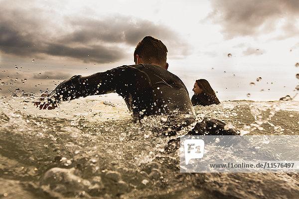 Zwei Freunde im Meer  paddeln auf Surfbrettern  Rückansicht