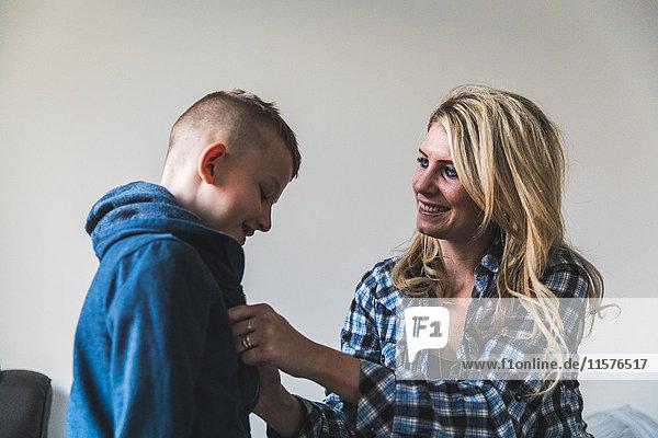 Mutter hilft kleinem Sohn beim Anziehen