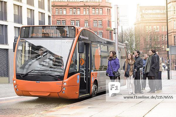 Fahrgäste an Bushaltestelle warten auf Einstieg in Elektrobus