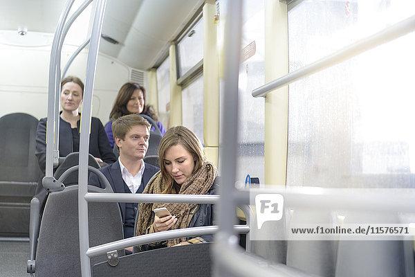 Fahrgast mit Smartphone im Elektrobus