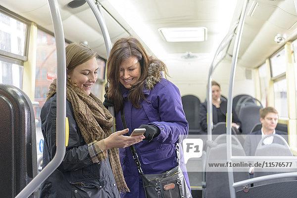 Fahrgäste schauen auf Smartphone im Elektrobus